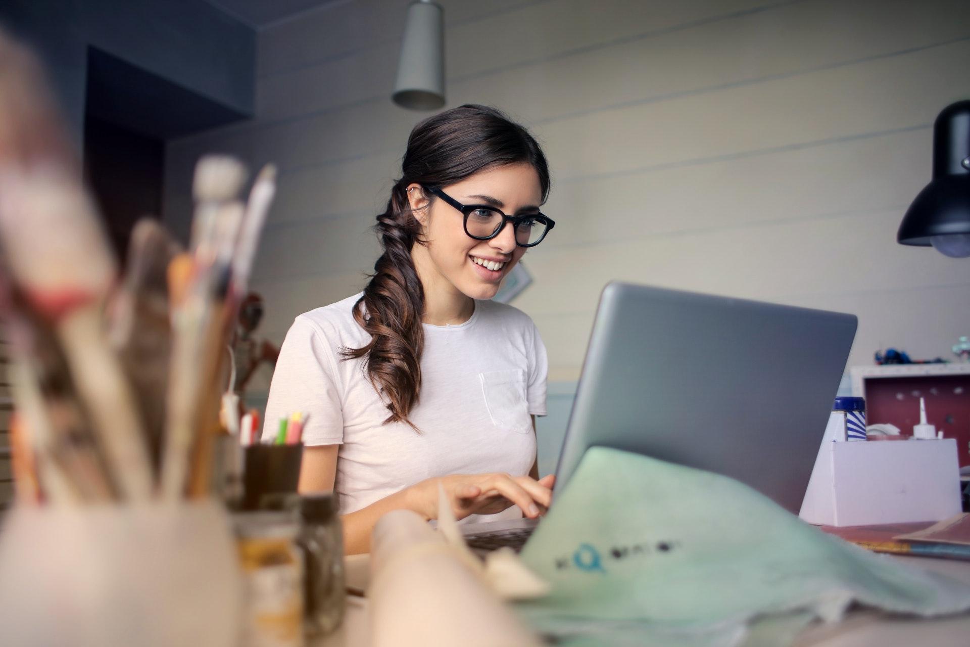 Uśmiechnięta kobieta przed komputerem