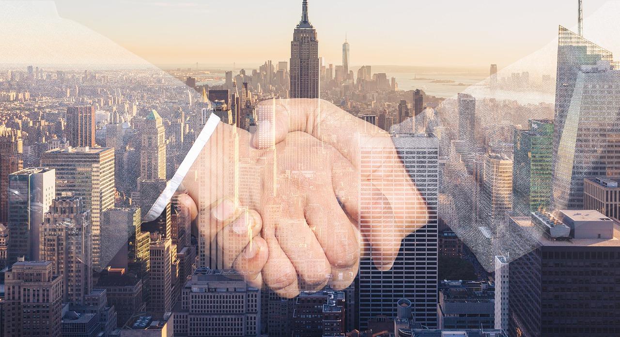 Uścisk dłoni odzwierciedlający porozumienie we wspólnym przedsięwzięciu na tle wieżowców w mieście