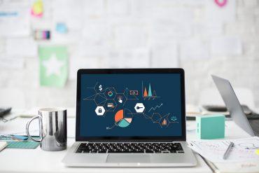 Laptop z otwartym raportem na biurku