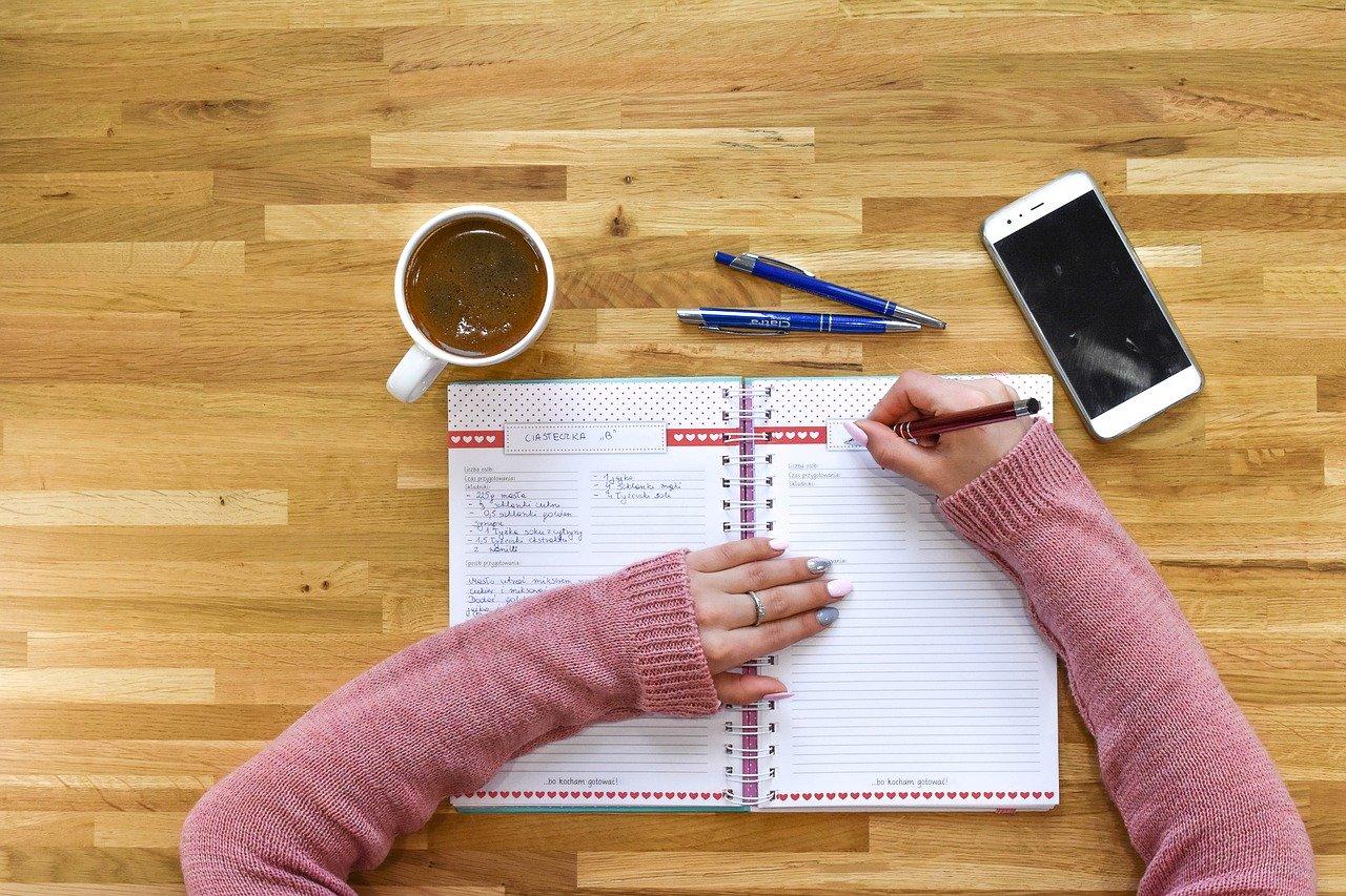 Kobieta pisze ręcznie w zeszycie