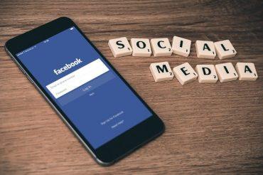 Telefon z włączoną stroną facebook leży na stole