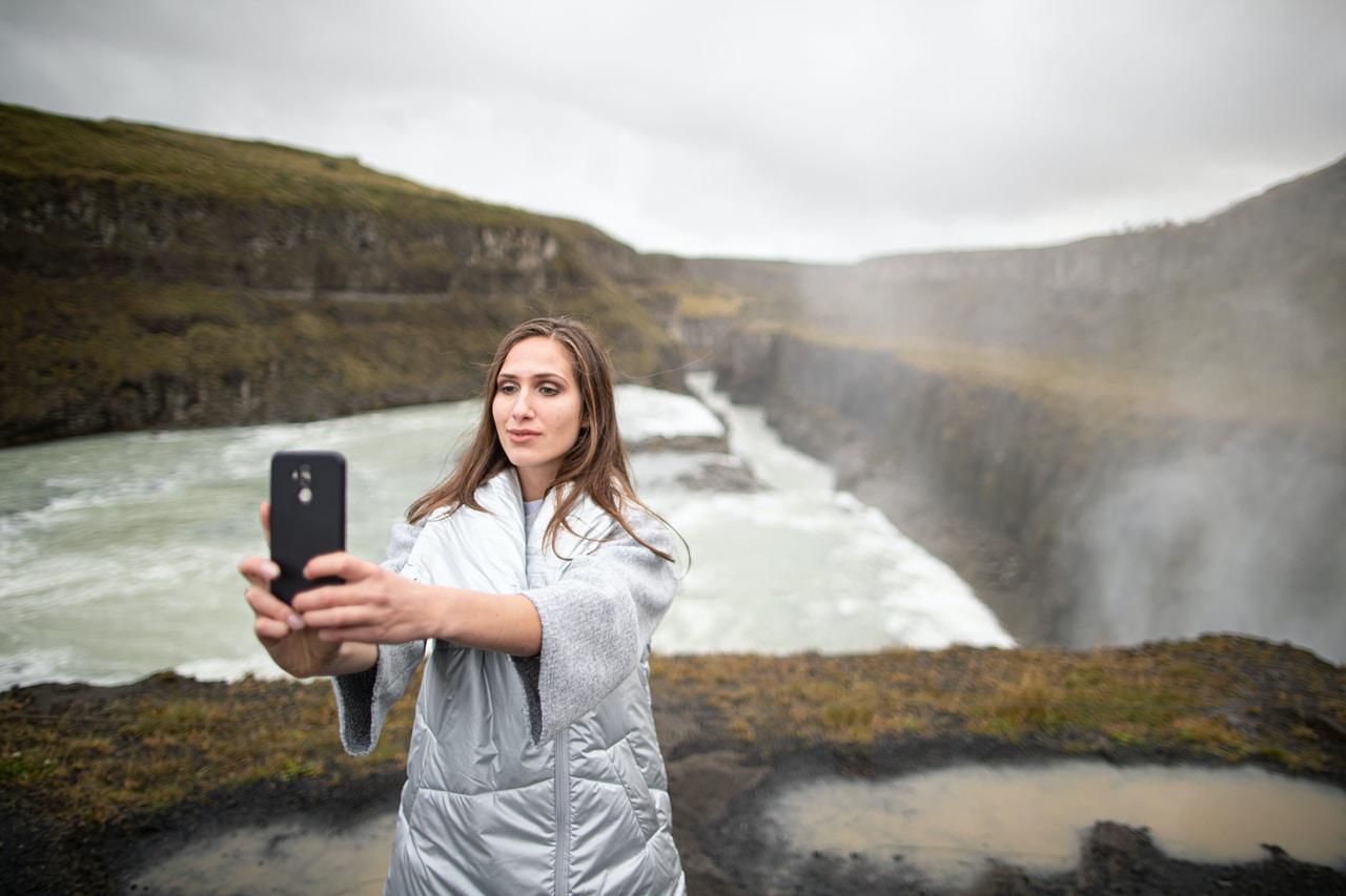 Kobieta z telefonem robi zdjęcie w miejscu gdzie łatwo rozbić szybkę
