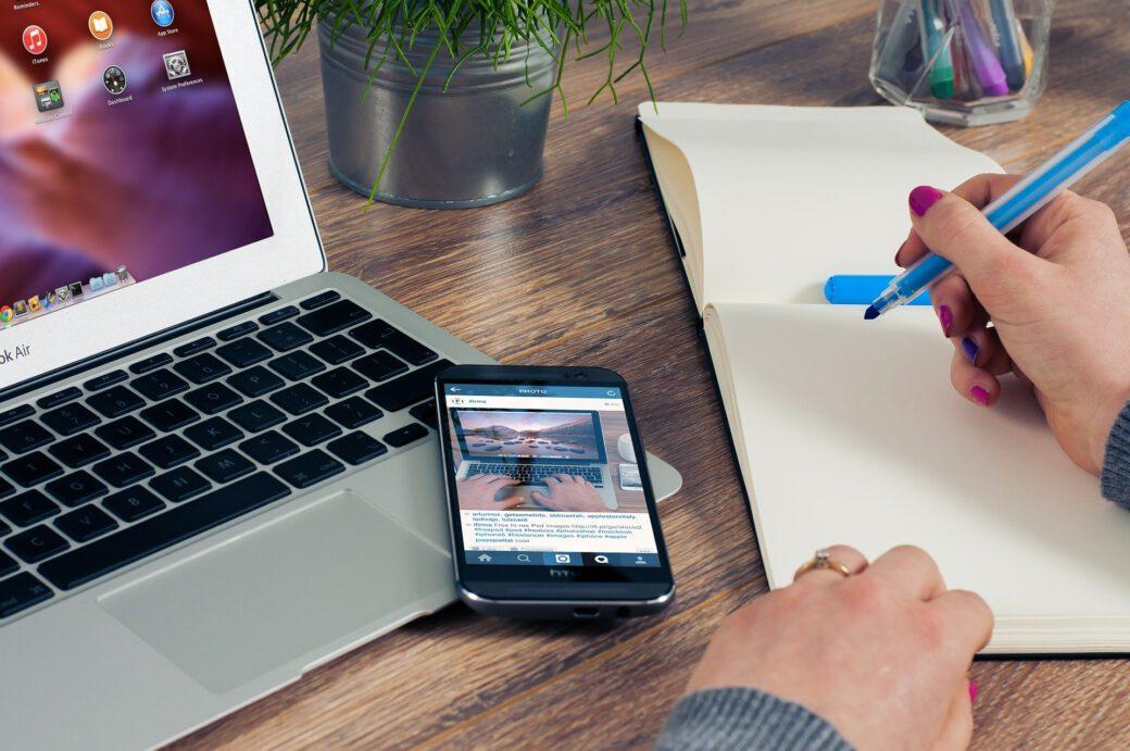 Kobieta w biurze pisząca coś na kartce. Obok jest telefon i laptop