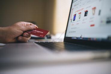 Dłoń która trzyma kartę bankową w dłoni przed laptopem