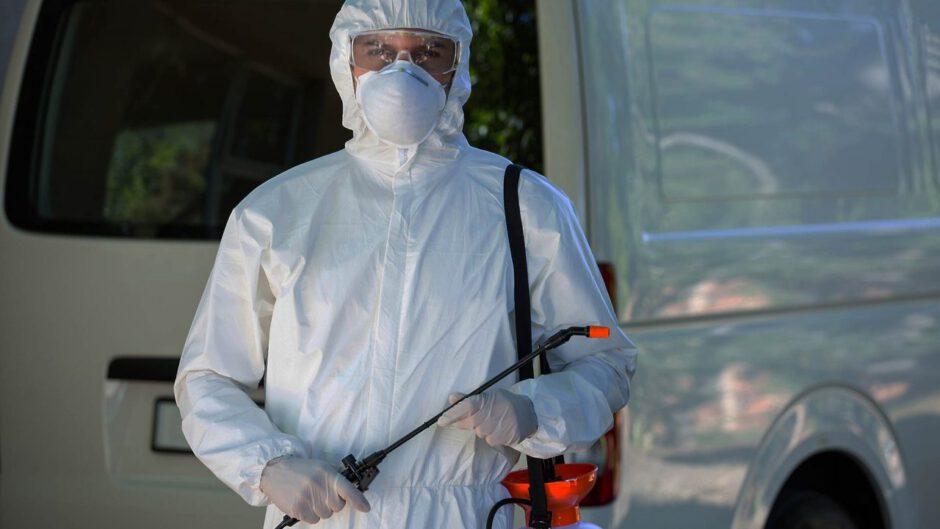 mężczyzna ubrany w strój ochronny do dezynfekcji