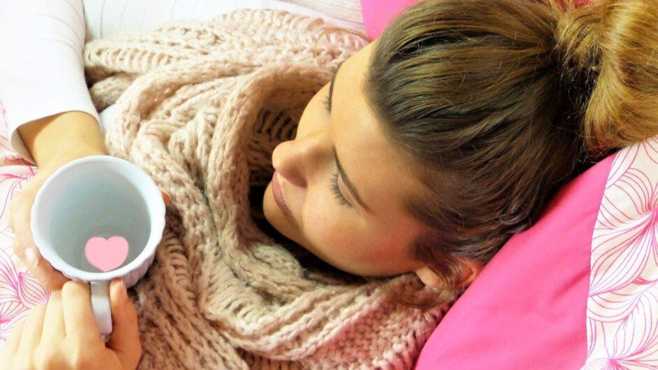 kobieta leżąca w łóżku trzymająca kubek w dłoniach