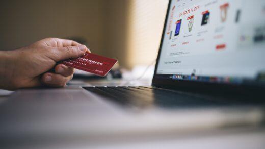 dłoń trzymająca kartę do bankomatu przy laptopie