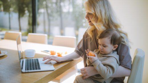 kobieta pracująca zddalnie, która trzyma dziecka na kolanach