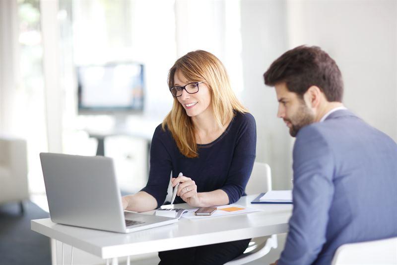 kobieta pokazująca na laptopie mężczyźnie podpis elektroniczny