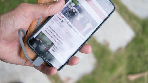 osoba trzyma telefon podłączony do powerbanka