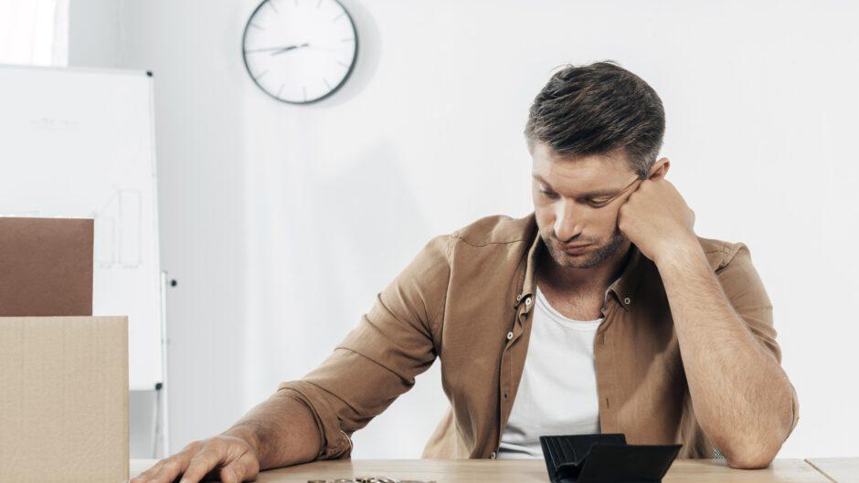 Bezrobotny mężczyzna siedzący prze biurku, patrzący na wysypane drobne pieniądze i zastanawiający się jaka jest stopa bezrobocia i ile osób jest w podobnej sytuacji do niego
