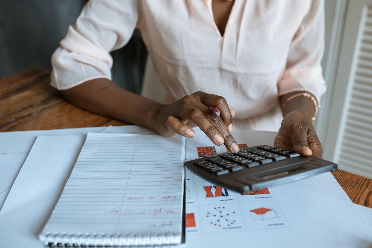 Kobieta licząca na kalkulatorze, zajmująca się finansami