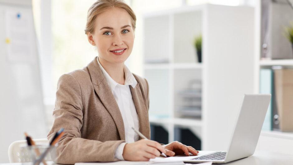 Kobieta pracująca w biurze rachunkowym, przygotowująca bilans finansowy oraz sprawozdanie za poprzedni rok obrotowy