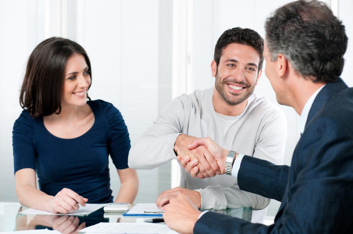 Zadowolona para, rozmawiajaca z pracownikiem banku komercyjnego, który przekazał im pozytywną decyzję o zdolności kredytowej