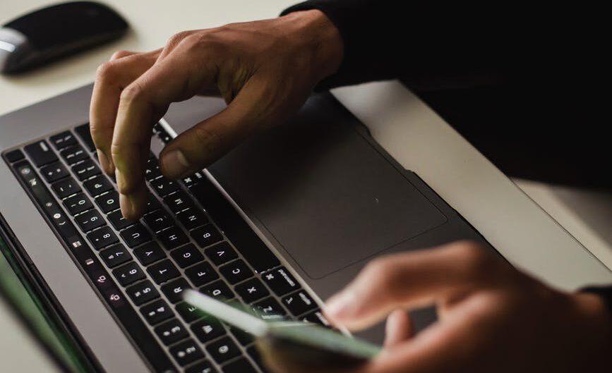Mężczyzna piszący na klawiaturze laptopa.
