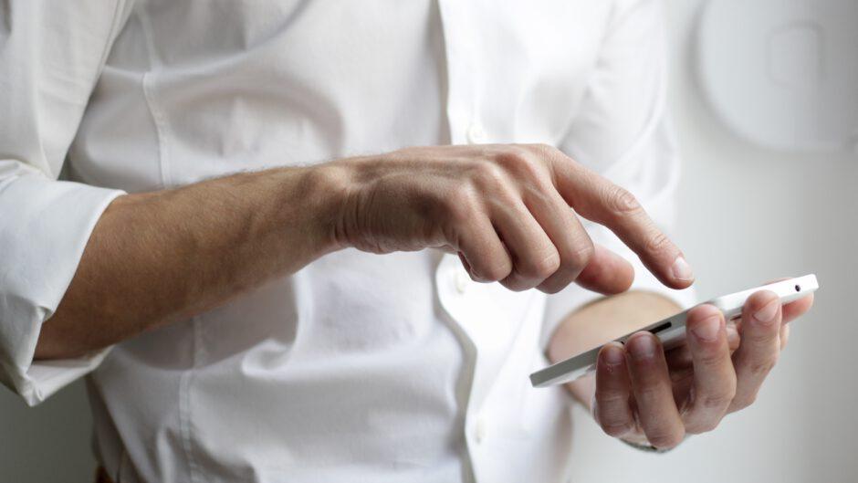 Mężczyzna trzyma telefon komórkowy.