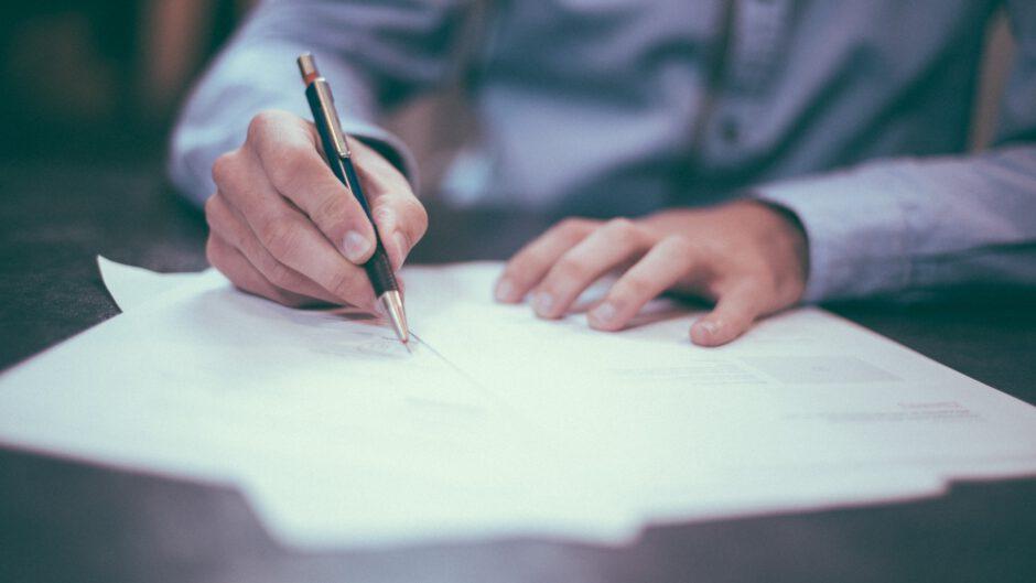 Mężczyzna podpisuje dokumenty do kredytu u doradcy finansowego