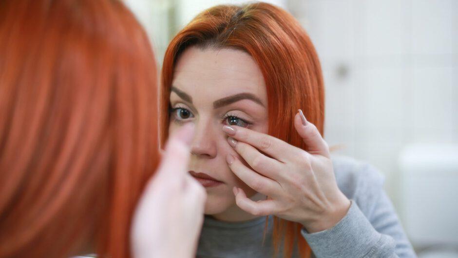 Kobieta aplikuje soczewki na oczy