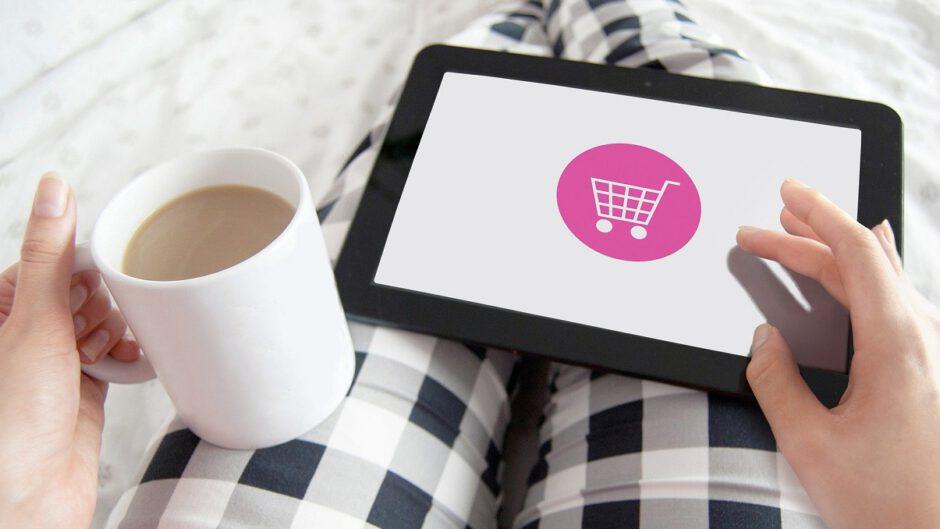 Kobieta z tabletem na kolanach lezy w łóżku i kupuje przez internet